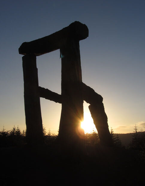 Silhouette of giant chair sculpture against a sunset