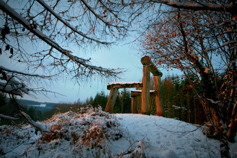Sculpture of a wooden chair in a forest in the snow