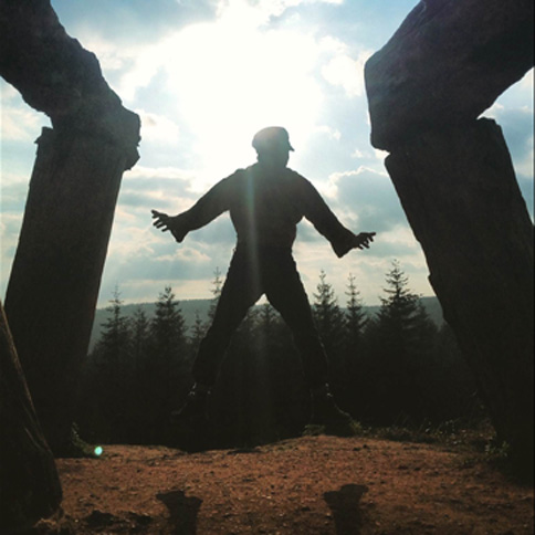 Silhouetted figure standing with arms out at the foot of giant sculpture
