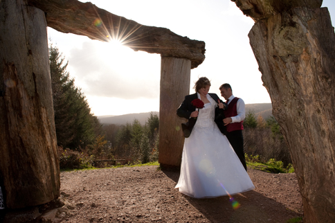 A newly married couple stand at the foot of a wooden sculpture, a sunset behind them